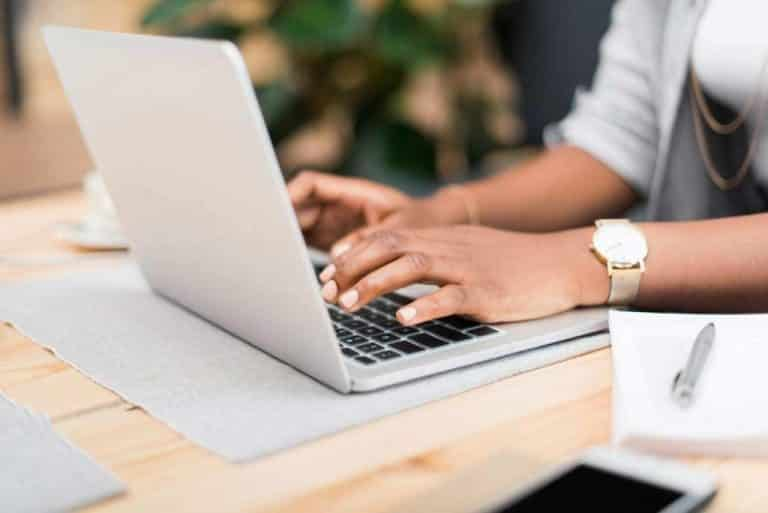 Close-up of businesswoman's hands typing on laptop