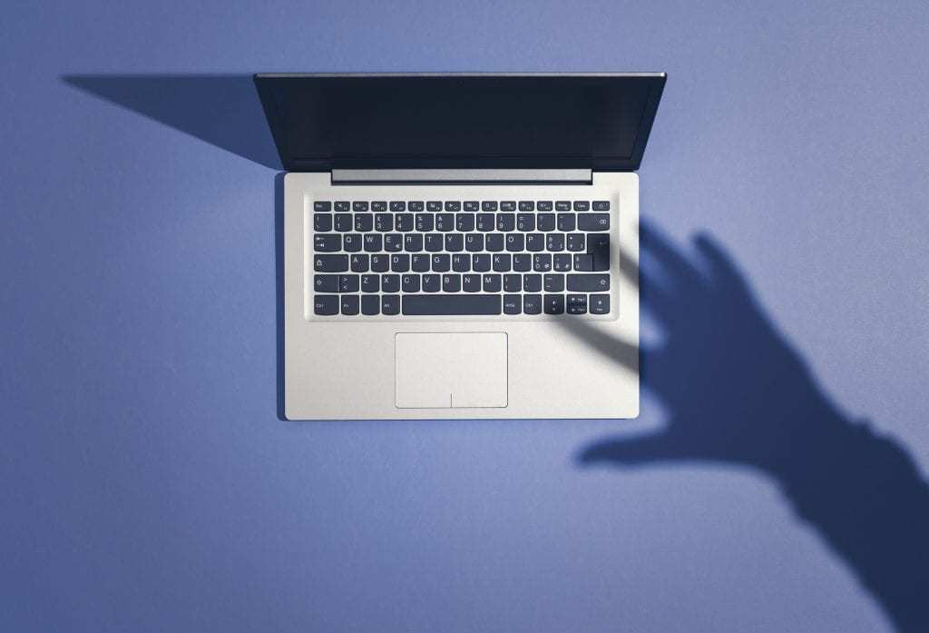 Laptop from above, shadow of a hand hovering above the keywboard