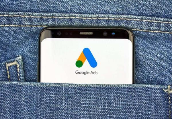 Google Ads Logo on a Phone Screen Peeking Out of Someone's Jeans Pocket