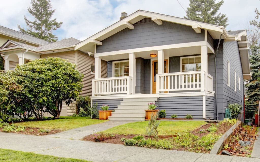 Blue grey smal craftsman style house with white porch.