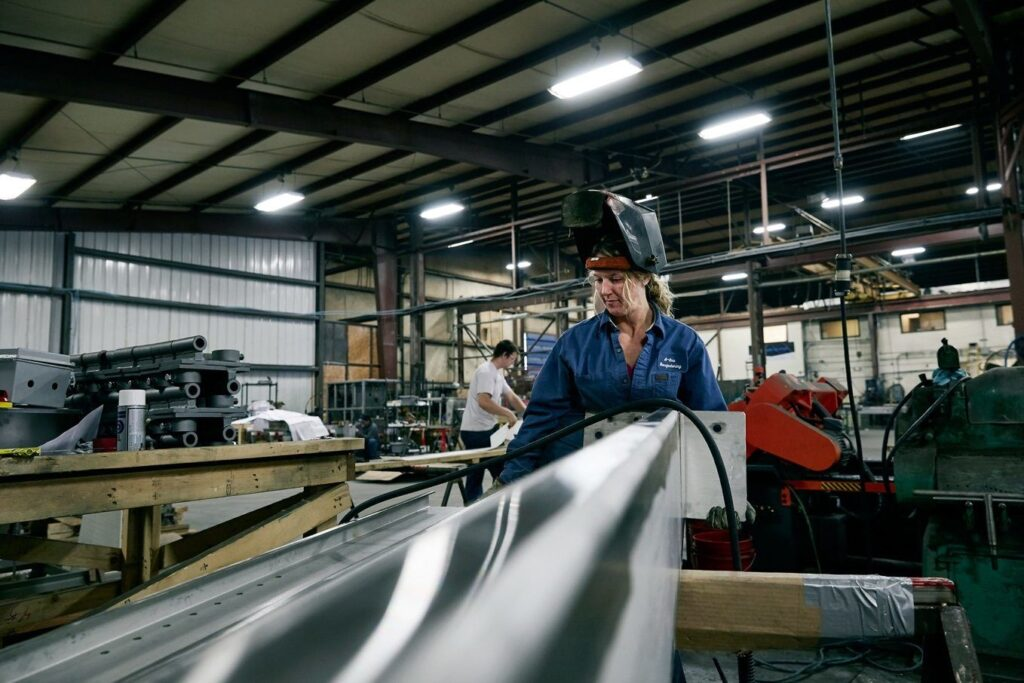 woman working on factory floor with protective face shield