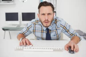 Young man in shirt and tie looking confusedly at computer